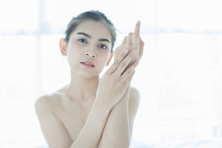 moisturize: A beautiful woman asian using a skin care product, moisturizer or lotion taking care of her dry complexion. Moisturizing cream in female hands .