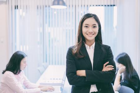 Asiatische Geschäftsfrauen und Gruppe unter Verwendung des Notizbuches für das Treffen und Geschäftsfraulächeln glücklich für das Arbeiten Standard-Bild