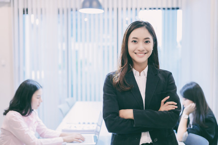 Asian business women and group using notebook for meeting and business women smiling happy for working