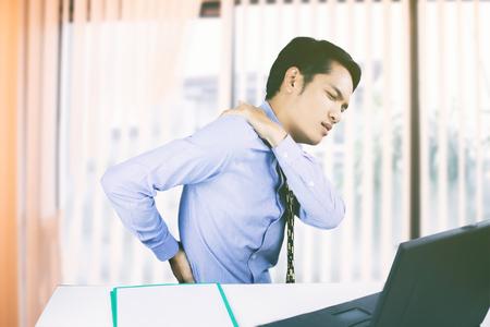 Aziatische zakenmensen met rugpijn zondigen een kantoor en serieus over het werk gedaan tot de hoofdpijn op hard werken