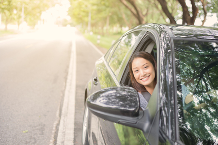 Beautiful Asian woman smiling and enjoying.driving a car on road for travel Stock Photo