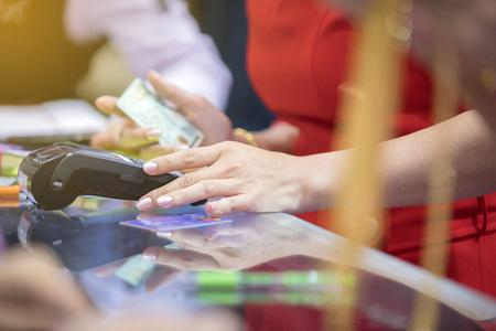 아시아 비즈니스 여성의 손을 카페테리아 및 슈퍼마켓에서 지불을 위해 컴퓨터를 스와핑 신용 카드를 사용 하여