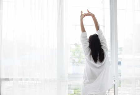 Asian woman waking up in her bed fully rested and open the curtains in the morning to get fresh air. Stockfoto
