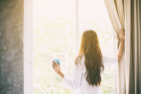 balcony: Asian women drinking coffee and waking up in her bed fully rested and open the curtains in the morning to get fresh air on sunshine