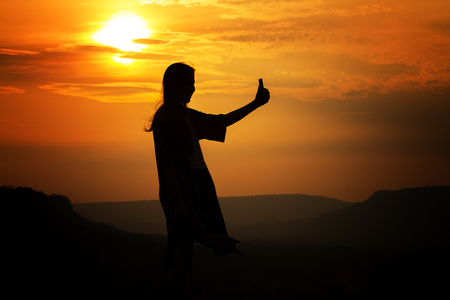 silhouette of Asian women photography and selfie with mountain at sunset .