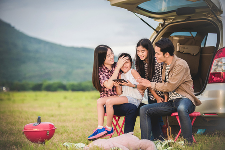 Happy little girl  with asian family sitting in the car for enjoying road trip and summer vacation in camper van Foto de archivo