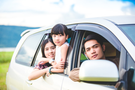 Happy little girl  with asian family sitting in the car for enjoying road trip and summer vacation in camper van Фото со стока