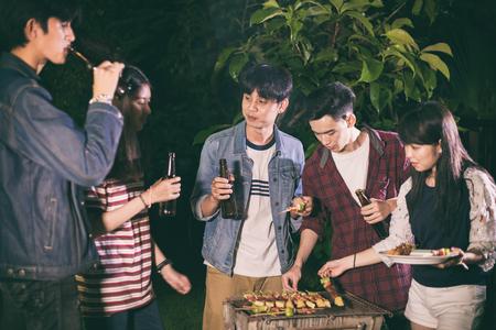 Grupo asiático de amigos que tienen jardín al aire libre barbacoa riendo con bebidas alcohólicas de cerveza en la noche Foto de archivo - 86799317