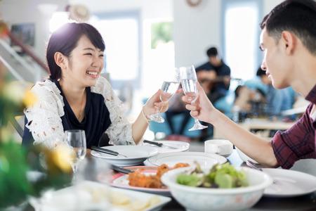Azjatycka młoda para delektuje się romantyczną kolacją wieczorem, siedząc przy stole w kuchni razem