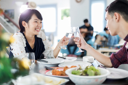 Asian young couple enjoying a romantic dinner  evening drinks while sitting at the dinning table on the kitchen together