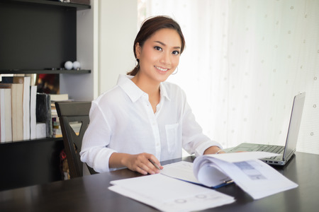 beautiful Asian business women checking document and using notebook and  smiling happy for working