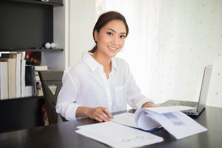 mooie Aziatische bedrijfsvrouwen die document controleren en notitieboekje gebruiken en gelukkig glimlachen voor het werken