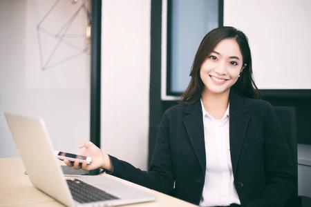 Asiatische Geschäftsfrauen und Gruppe unter Verwendung des Notizbuches für das Treffen und Geschäftsfraulächeln glücklich für das Arbeiten