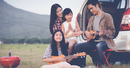 happy little girl playing ukulele with asian family sitting in the car for enjoying road trip and summer vacation,soft focus
