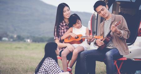 heureuse petite fille jouant ukulélé avec la famille asiatique, assis dans la voiture pour profiter de voyage sur la route et les vacances d'été, flou artistique