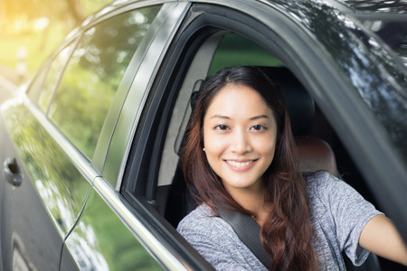 Beautiful Asian woman smiling and enjoying.driving a car on road for travel Фото со стока