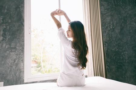 그녀의 침대에서 깨어 난 아시아 여성은 신선한 공기를 얻기 위해 아침에 커튼을 완전히 열었습니다. 스톡 콘텐츠 - 87961859