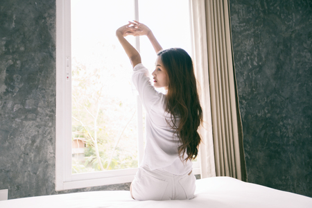 Asian woman waking up in her bed fully rested and open the curtains in the morning to get fresh air. Banco de Imagens