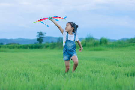 Asian child girl with a kite running and happy on meadow in summer in nature Foto de archivo