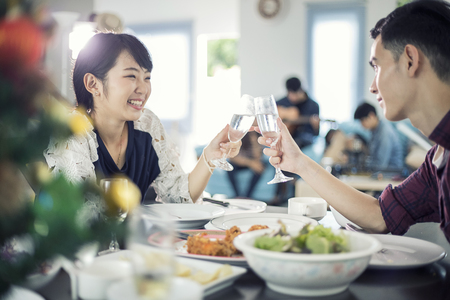 Asian young couple enjoying a romantic dinner  evening drinks while sitting at the dinning table on the kitchen together,soft focus