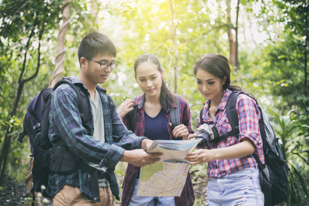 Asian Group of young people Hiking with friends backpacks walking together and looking map and taking photo camera by the road and looking happy ,Relax time on holiday concept travel Archivio Fotografico