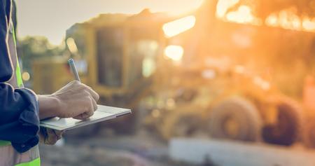 Ingegnere asiatico con l'elmetto protettivo che utilizza il computer del pc della compressa che ispeziona e che lavora al cantiere