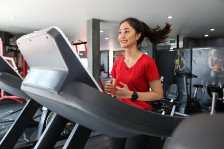 Azjatyckie kobiety biegają w butach sportowych na siłowni, podczas gdy młoda kobieta rasy kaukaskiej ma jogging na bieżni