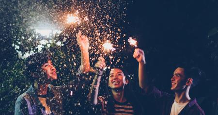 Groupe asiatique d'amis ayant barbecue de jardin en plein air en riant avec des boissons alcoolisées et montrant un groupe d'amis s'amusant avec des cierges magiques la nuit, soft focus Banque d'images