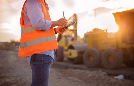 Ingeniero asiático con casco usando computadora tablet pc inspeccionando y trabajando en el sitio de construcción