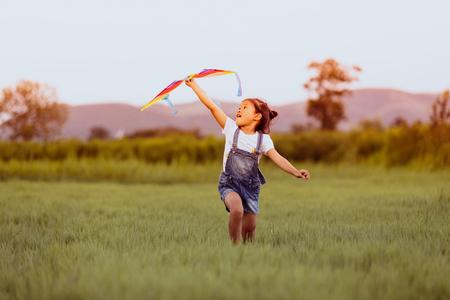 Niña asiática y padre con una cometa corriendo y feliz en la pradera en verano en la naturaleza