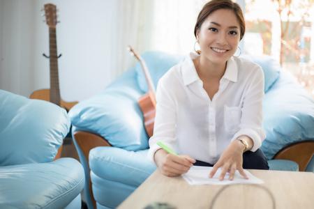 Mooie Aziatische zakelijke vrouwen schrijven van gegevens document controleren en glimlachen gelukkig voor het werken Stockfoto - 98001751
