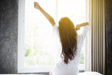 Donna asiatica Bella giovane donna sorridente seduto sul letto e che si estende al mattino in camera da letto dopo essersi svegliato nel suo letto completamente riposato e aprire le tende al mattino per ottenere aria fresca. Archivio Fotografico