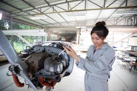 Hombres y mujeres asiáticos Ingenieros y técnicos están reparando aviones. Editorial