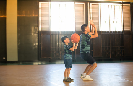 Asian family playing basketball together. Happy family spending free time together on holiday