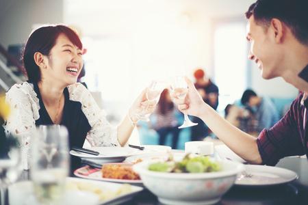 Jeune couple asiatique bénéficiant d'un dîner romantique en soirée tout en étant assis à la table à manger sur la cuisine ensemble, soft focus