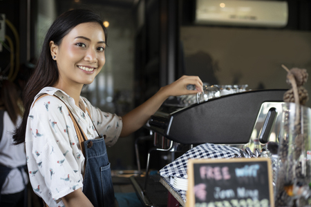 Asian women Barista smiling and using coffee machine in coffee shop counter - Working woman small business owner food and drink cafe concept Imagens