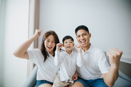 Excited and Happy family with arms raised while watching television at home