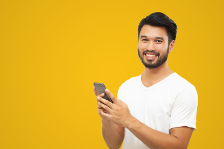 Asian business man handsome man with a mustache, smiling and laughing and using smart phone on yellow background