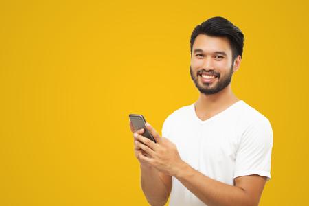 Asiatischer Geschäftsmann gutaussehender Mann mit Schnurrbart, lächelnd und lachend und mit Smartphone auf gelbem Hintergrund