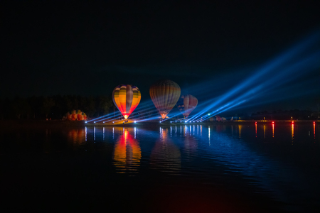 Colorful hot air balloons flying over river on night festival