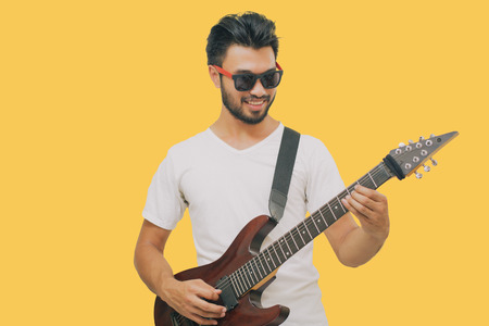 Handsome young asian men playing guitar and  listen music with headphones  isolated on yellow background Stok Fotoğraf