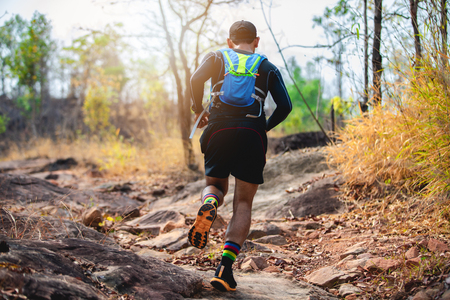 A man Runner of Trail . and athlete's feet wearing sports shoes for trail running in the forest 版權商用圖片