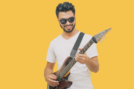 Handsome young asian men playing guitar and  listen music with headphones  isolated on yellow background Zdjęcie Seryjne