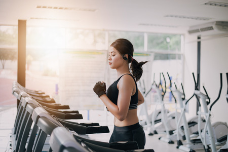 Asian women running sport shoes at the gym while a young caucasian woman is having jogging on the treadmill Фото со стока
