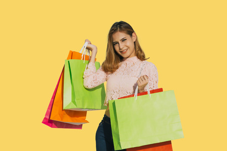 Asian women Beautiful girl is holding shopping bags and smiling on yellow background