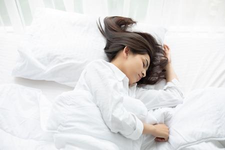美しいアジアの女性が白いベッドでバスケットと寝ています。