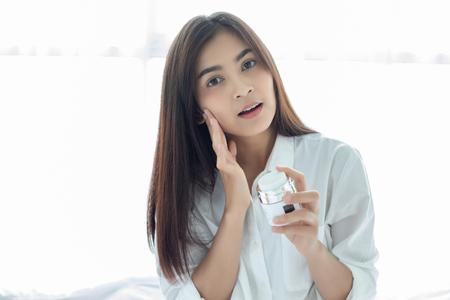 Eine schöne asiatische Frau, die ein Hautpflegeprodukt, eine Feuchtigkeitscreme oder eine Lotion verwendet, die sich um ihren trockenen Teint kümmert. Feuchtigkeitscreme in weiblichen Händen. Standard-Bild