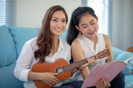 Two asian women are having fun playing ukulele and smiling at home for relax time