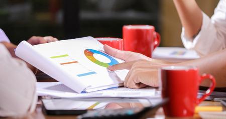アジアのビジネスウーマンは、バックグラウンドで動作するラップトップコンピュータとグラフ財務図を持つオフィステーブル上の文書を分析します 写真素材