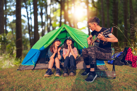 A group of Asian friends tourist drinking and playing guitar together with happiness in Summer while having camping